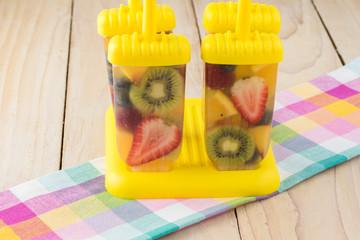 Assorted fruit and berries in grape juice in ice pop molds.