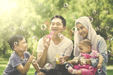 Muslim family playing with soap bubble
