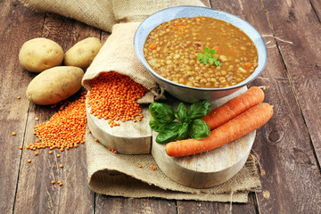 Lentil soup with potato in a bowl on a wooden background