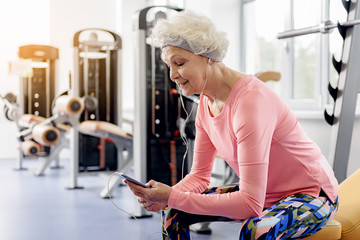 Smiling grandmother hearing song in fitness center