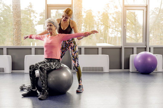 Smiling coach training old woman in gym