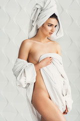 gorgeous sexy young girl with dark hair, big eyes and dark eyebrows wearing white bath robe whith towel on her head.