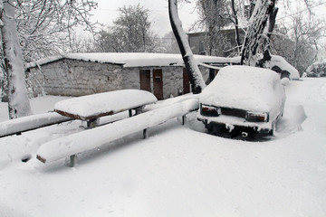 The car is covered with snow. Big snow covered the earth, buildings, roofs and transport