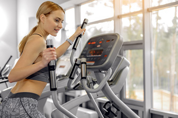 Happy woman running on cross trainer