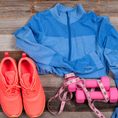 Gym outfit - workout clothing, sneakers, dumbbells, and measure.