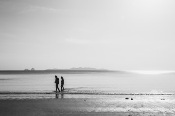 friends walking in the sea beach, lonely summer season vintage color tone.