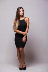 Full length portrait of a sexy woman in little black fashion dress on grey