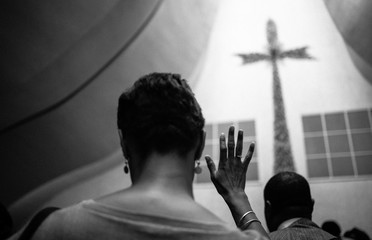 A black woman crosses her fingers in the church.  Fototapete