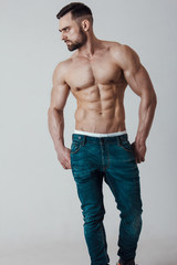 Muscle male model with muscular body in jeans posing on grey background. Studio shoot.