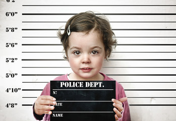Little child posing with a prison board