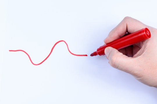 Hand holding a red pen having drawn a wavey line isolated on white background