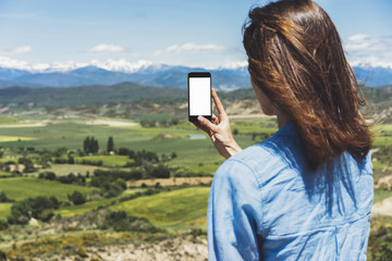 Hipster photograph on smart phone gadget mobile, mock up of blank screen. Girl traveler hold in hand mobile on background mountain landscape horizon. Tourist look map on adventure trip