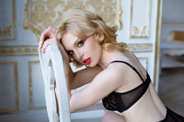 Female portrait of cute lady in black bra indoors. Close up beautiful sexy model girl in elegant pose. Closeup beauty blonde woman with hairstyle
