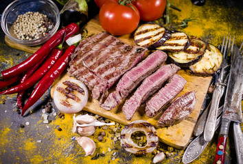 Rare roast sirloin of beef with grilled vegetables and spices on rustic chopping board on dark background. Food background. Selective focus.