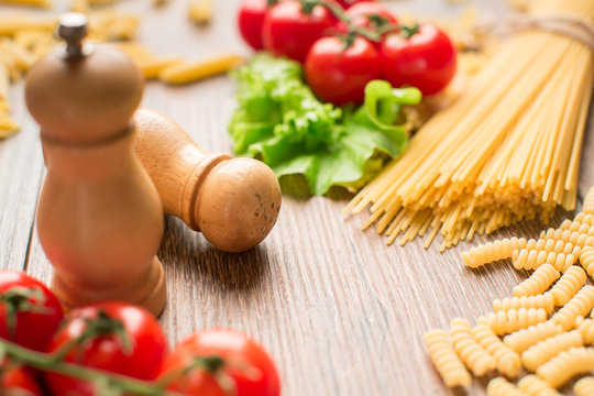 pasta with tomatoes and basil on wooden table