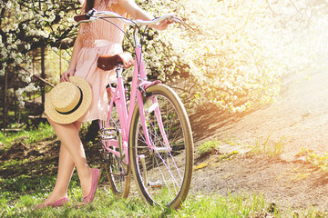 Vintage bike concept. Beautiful and young girl in pink dress standing with retro bike on green grass and keeping hat. Flower background.