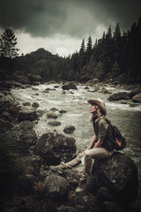 Beautiful woman hiker near wild mountain river.