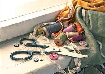 Old scissors, spools of thread, fabric and buttons on the windowsill.