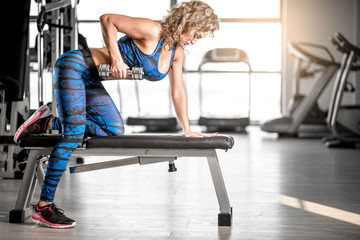 Female one-arm dumbbell rows in modern gym