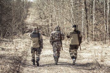 Group of men hunters outgoing on rural road during hunting season