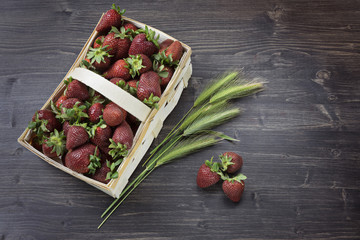 Wicker basket with juicy fresh strawberries on the wooden background high angle view summer concept