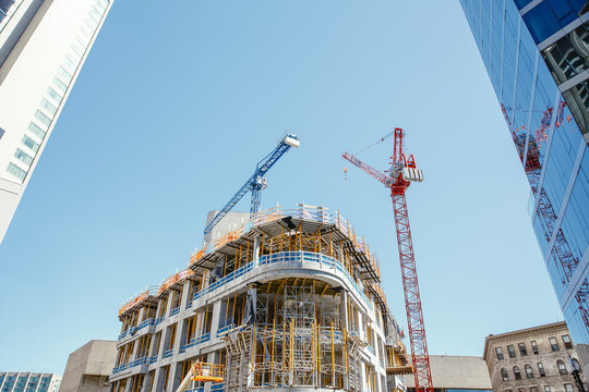 Construction of a high-rise building in the city center. Crane and building under construction in the scaffolds against a background of blue sky