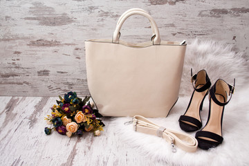 Fashionable concept. Light bag, black shoes and flowers on a white fur