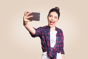 Young beautiful happy woman in casual style holding phone and doing selfie with smart phone. studio shot on beige background.