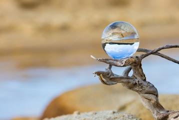 Glaskugel auf Ast in einer trockenen Landschaft