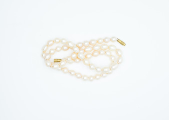 on a white background lies a pink pearl necklace on the neck