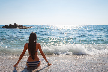 Sexy back of a girl with long hair in blue swimsuit sits on the sand on the beach against the sea, small pebbles, pleasure, tourism.