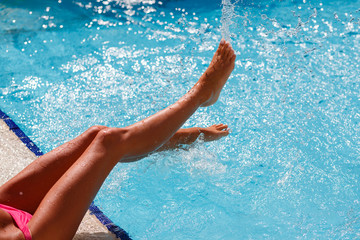 Female foot in blue water. Feet splashing in the pool. Blue water in the pool is splashes from female legs. Women's legs playing with water in a swimming pool. Woman frolicking in the pool.