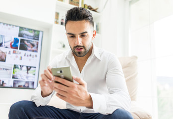 Young good looking man at home using a phone
