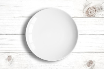 Top view of blank white dish on a wood background.