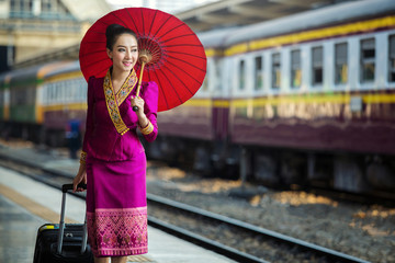 Asian woman in traditional dress waiting for train at Hualamphong Railway Station in thailand