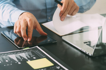 close up of businessman working with smart phone and digital tablet and laptop computer  on wooden desk in modern office with glass reflected view