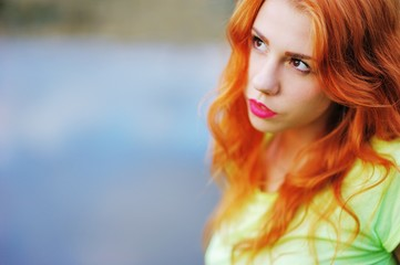 Portrait of a very beautiful brown eyed girls with bright red hair in a light green dress on a background of lake, close-up