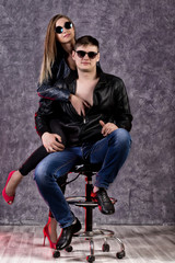 young beautiful girl and handsome guy in leather jackets posing on a high chair on gray background