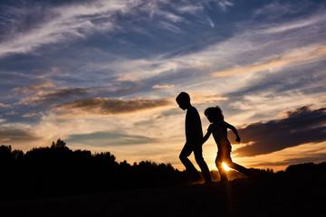 children running on the background of sunset sky