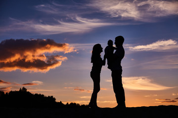 happy family playing on the sunset background