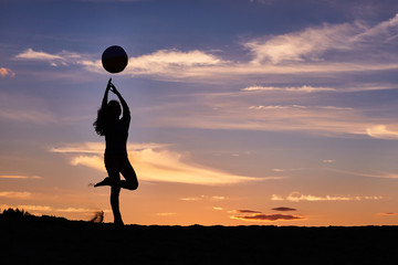 girl dancing with the ball on the sunset sky background