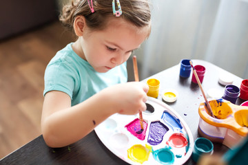 little girl mixes paint. child draws paints