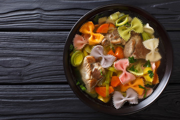 Delicious soup with meat, multi-colored farfalle pasta and vegetables close-up. Horizontal top view