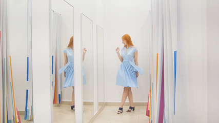 Young woman trying blue dress near mirror in fitting room at store