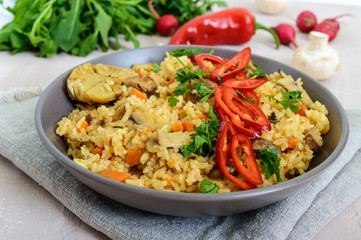 A traditional Asian dish - pilaf with meat, mushrooms and pepper capi in a bowl.