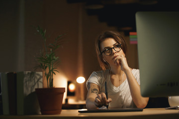 Serious woman designer using graphics tablet and computer