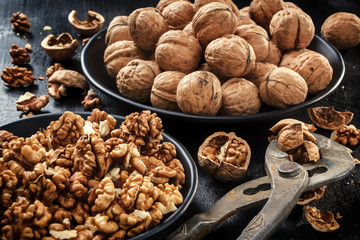 Walnuts. Nuts of walnuts.Tongs for cutting nuts. Pure organic walnuts. Nuts in black plates against the background of a black wooden background. Agriculture. Fresh autumn walnut harvest in the village