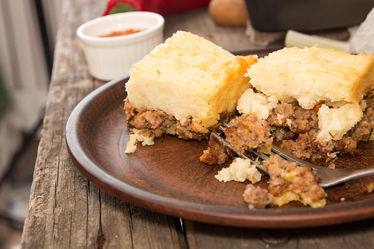 Shepherd's pie traditional english dish. Recipe with minced beef, lamb, carrot, onion, celery, mashed potato baked in casserole. Rustic style
