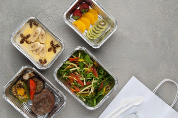 fast food in a foil box on a gray background. a healthy food close up. delivery from the restaurant a set of healthy food