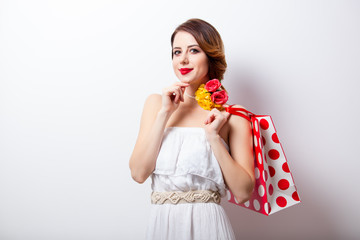 portrait of beautiful young woman with dotted shopping bag on the wonderful studio background